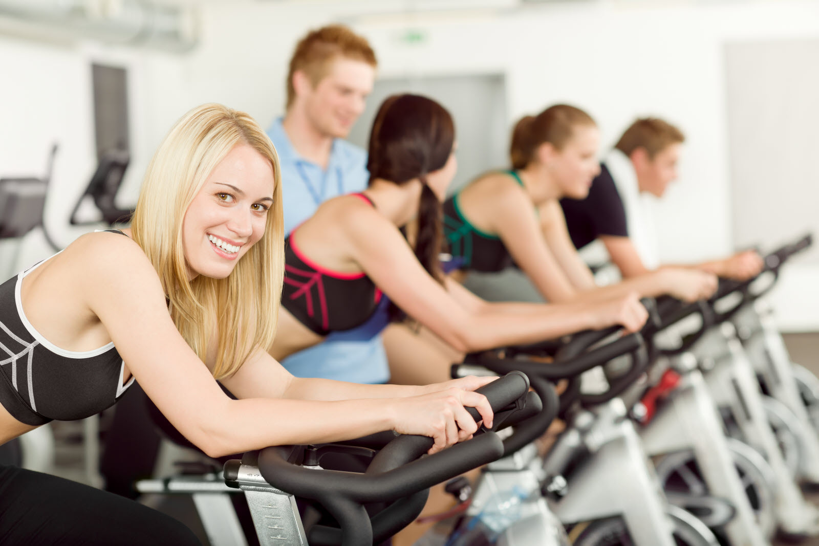 Young fitness people doing spinning with instructor at gym