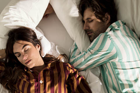 Man and woman sleeping dressed in stiped pyjamas