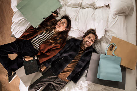 Couple lying on bed with shopping bags