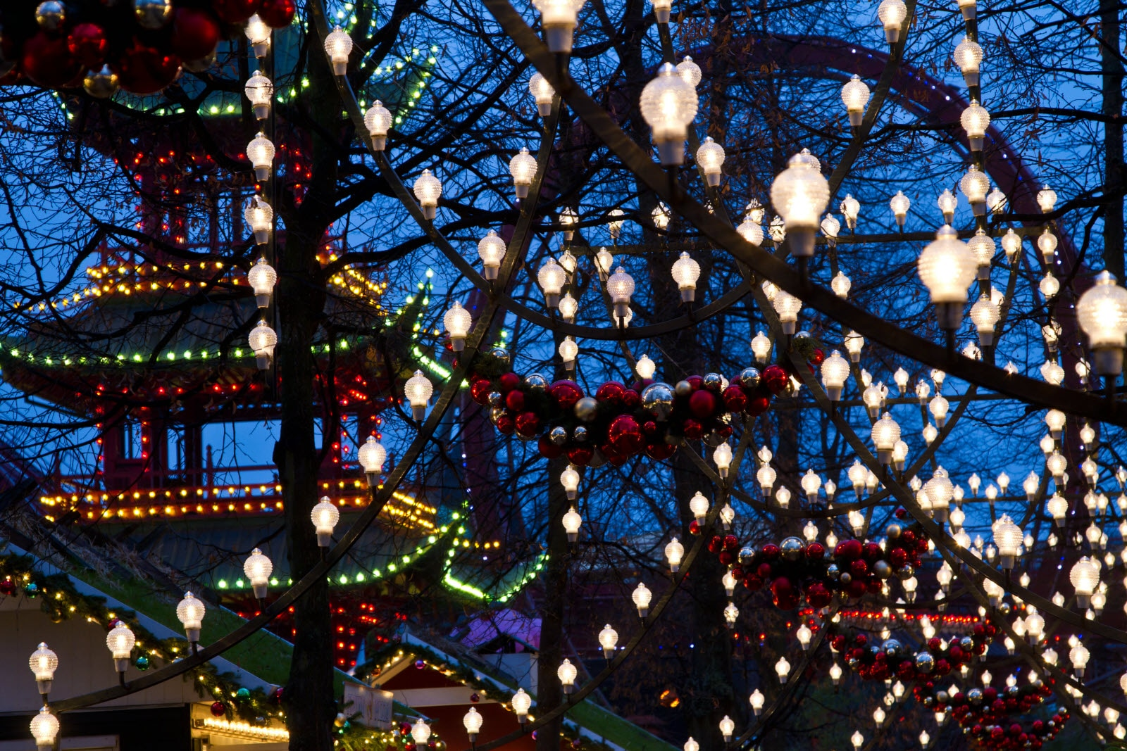 Christmas at the Tivoli in Copenhagen at night. The lights are bright.