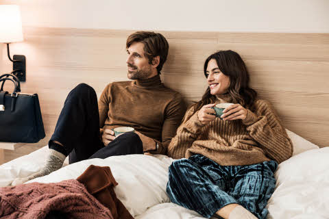 A couple drinking coffee in bed
