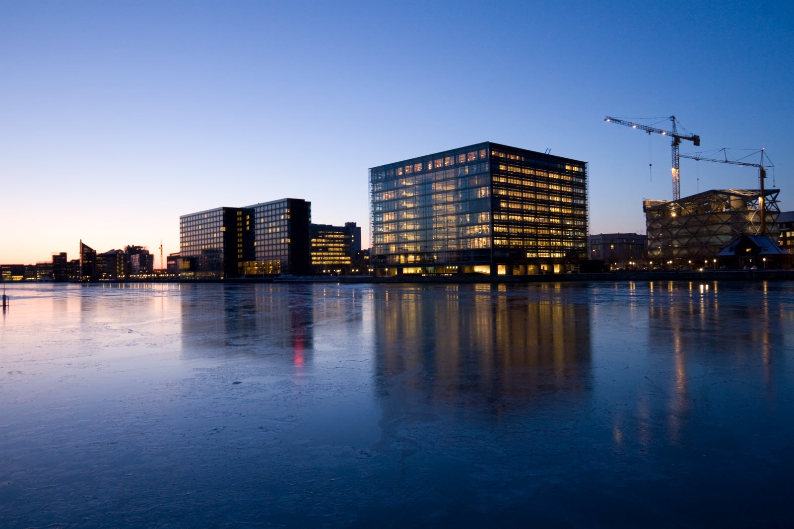 Icy waters in Copenhagen harbor at sundown on a cold winter day. The office buildings are still lit and a building is under construction on the far right.