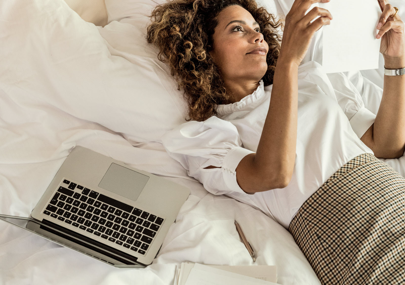 Woman working from bed.
