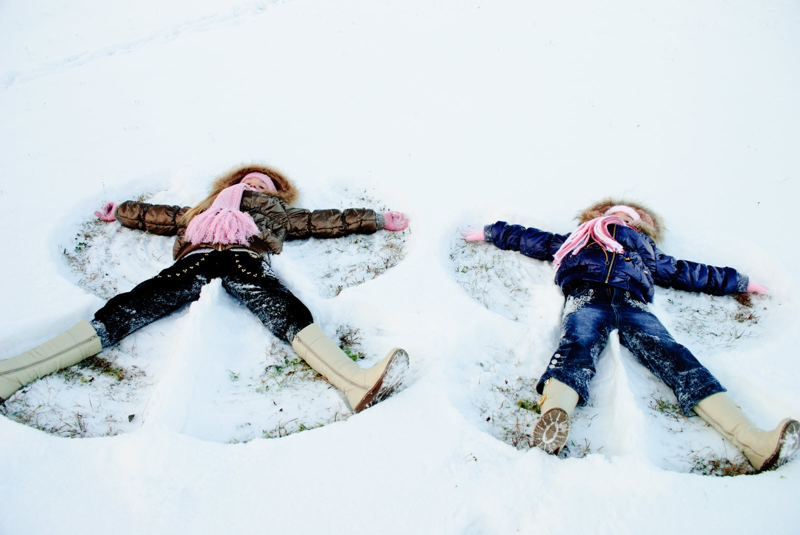 Two little sisters playing with snow outdoors. Making snow angels.